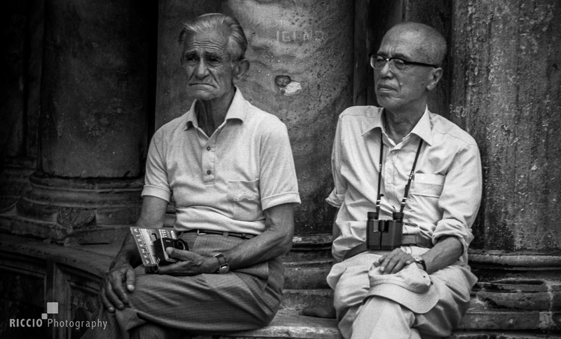 Asian and caucasian man sitting near each other in Venice. Photographed by Maurizio Riccio
